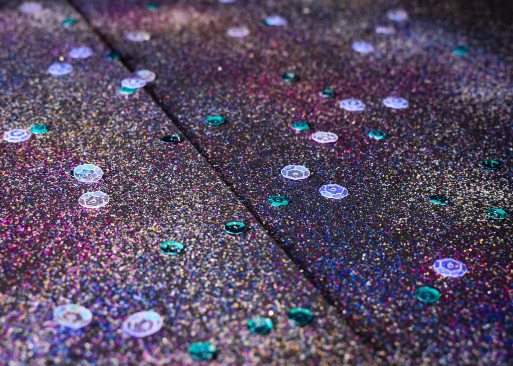 Glitter and sequins on black card background