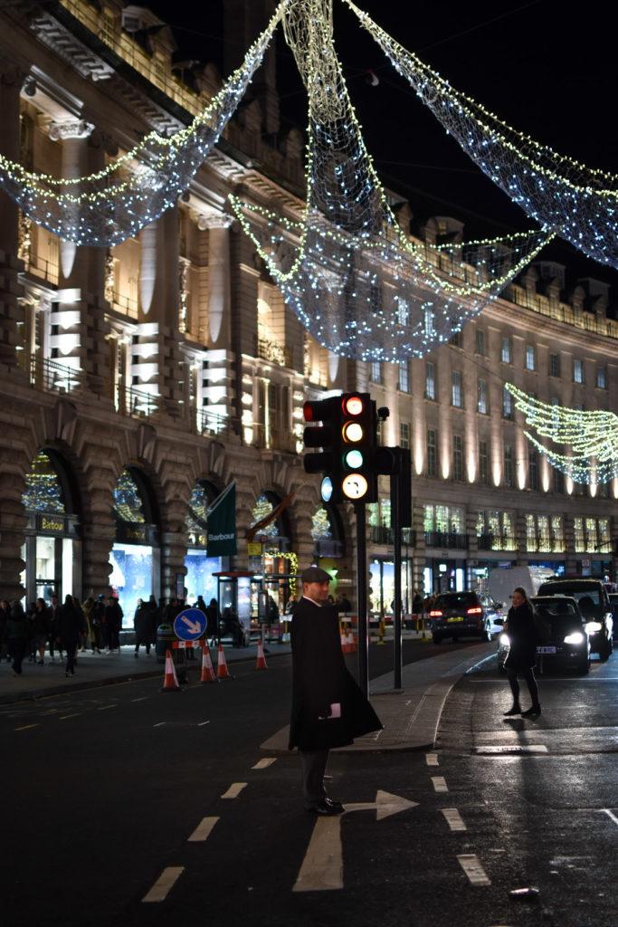 Man in flat cap, waiting at lights, on Regent Street, Christmas 2018